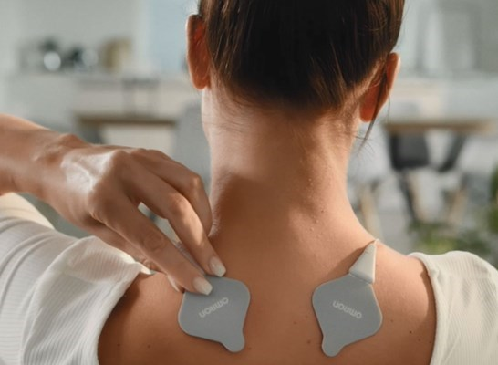 Woman using heat tens on back of shoulder